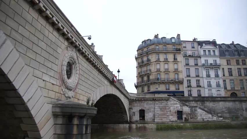 Paris streets view from a boat sailing over the Seine river showing a bridge and the grey and light brown french buildings apartments on the side of the Seine boating slowly along side of structures  | Shutterstock HD Video #8841028