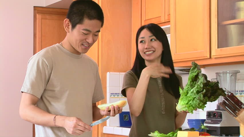 Happy young Asian couple preparing food in kitchen