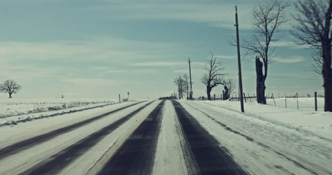 Driving in the middle of the winter, on a windy cold snowy day. POV dash cam style 4k footage on rural country roads.