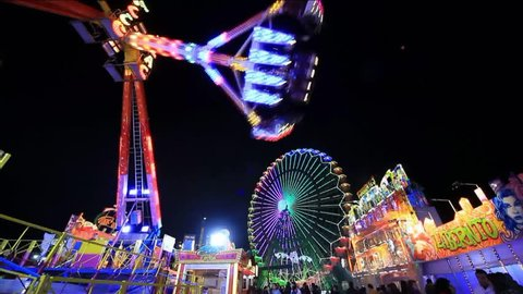 ALICANTE, SPAIN – JANUARY 10: Fireworks over amusement fair park at night with ferris wheel and carousels in Alicante city; on January 10, 2015 in Alicante.
