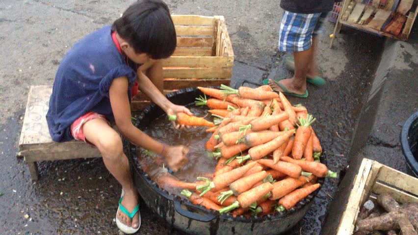 DAVAO/PHILIPPINES - FEBRUARY 21: Underage labor boy cleaning vegetables in the market on February 21st 2015. Violation of child rights and minors work is common in Asia and the Philippines