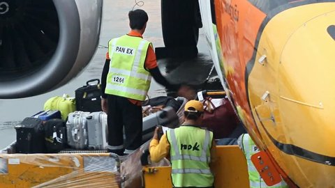 BANGKOK, NOV 17, 2014 - employees of the airline Nok Air unloaded luggage from the plane at the airport Don Mueang