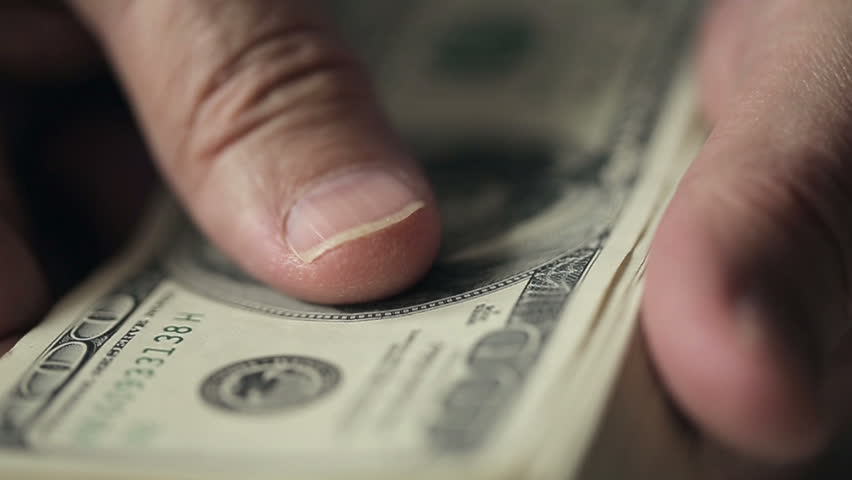 Close up a businessman's hands counting hundred dollar bills at a table. Slow motion