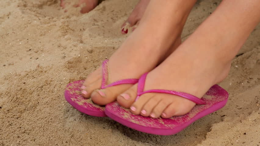 542cb116a A girl with pink summer sandal shoes on her feet relaxes on the beach and  plays with the sea sand and lets it slip between her toes on a sunny  holiday ...
