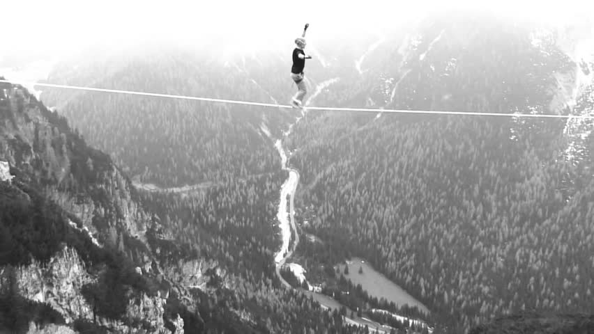 aerial shot of tightrope walker in the air in the mountain with snow black and white