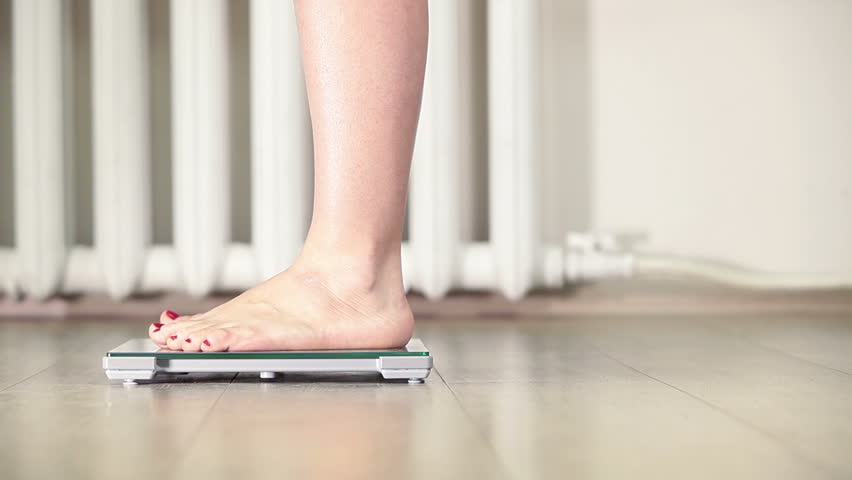 Human feet standing with wiggling toes when stepping on scales, close-up view | Shutterstock HD Video #8979562