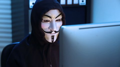 MOSCOW, RUSSIA - FEBRUARY 25, 2015:  The hacker in a mask of Guy Fawkes uses the computer late at night.
