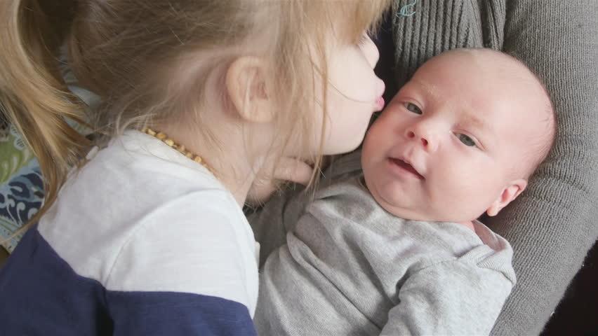 Newborn boy kissed by toddler sister   Shutterstock HD Video #8989558
