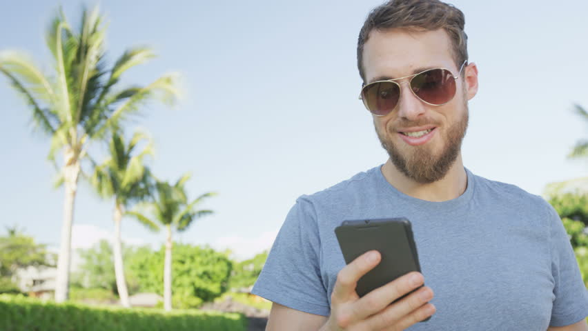 Man sms texting using app on smart phone outdoors in summer. Handsome young casual man using smartphone smiling happy wearing sunglasses. Urban male hipster. RED EPIC 90 FPS.