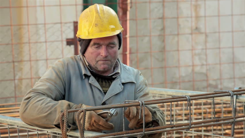 construction worker wearing helmet using a pliers to connect reinforcement bars at building site - Construction Laborer