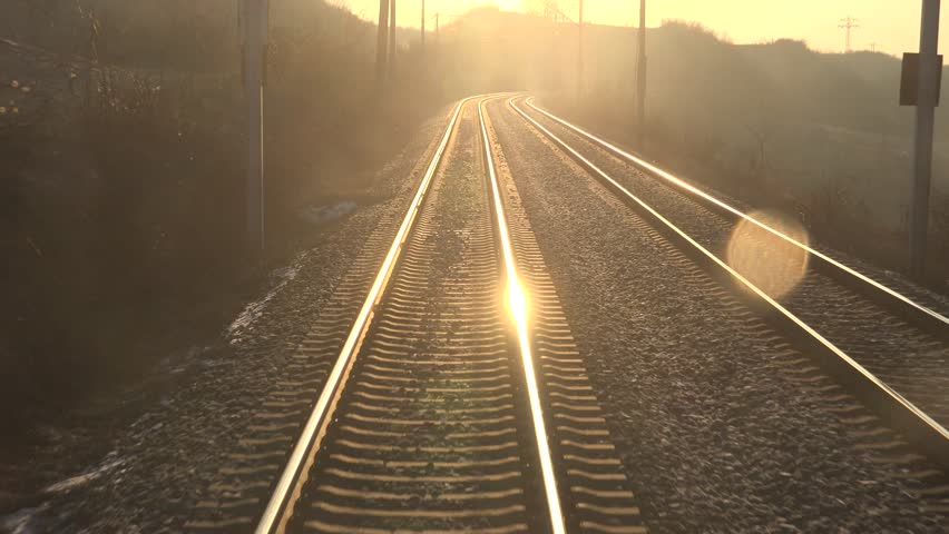 ULTRA HD 4K POV Point of view of train motion and sun ray, orange sunlight and parallel line track by day