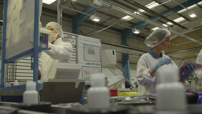 4K Pharmaceutical manufacturing facility factory. Pharma research and production science. Workers and technicians operate production machinery.  Drugs and cosmetics business industry.