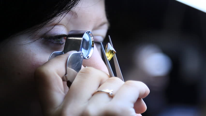 Girl with a magnifying glass looks at a diamond to determine its purity. | Shutterstock HD Video #9115940