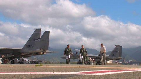 CIRCA 2010s - Pilots walk near their fighter jets.