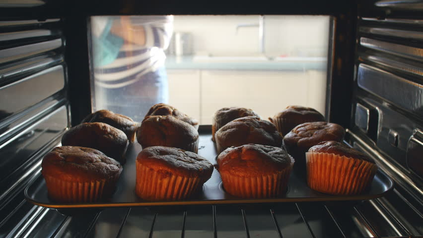 open oven door while baking. woman opens door of oven and takes out a tray freshly baked muffins. shot open while baking