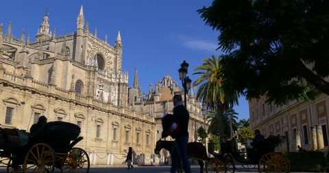 SEVILLE, SPAIN - JANUARY 2015: sun light city main cathedral square with horse tourist ride 4k circa january 2015 seville, spain.