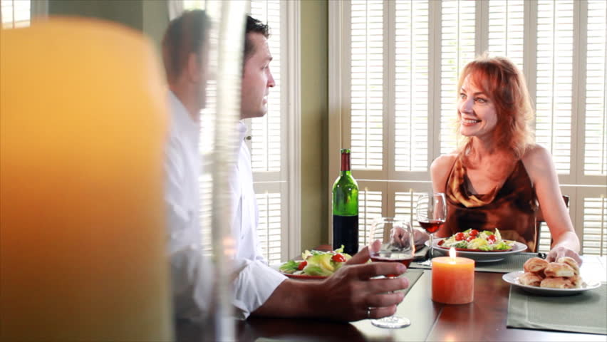 A couple enjoy wine, food, and lively conversation as they sit at a table in a sunlit room. Reveal shot. Dolly Shot