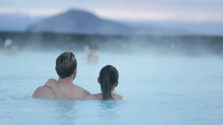 Hot spring geothermal spa on Iceland. Romantic couple in love relaxing in hot pool on Iceland. Young woman and man enjoying bathing relaxed in a blue water lagoon Icelandic tourist attraction. Sunset. | Shutterstock HD Video #9247742