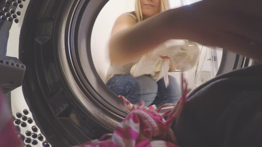 Housework. Beauty Young woman doing laundry. Girl portrait from inside of washing machine. Happy young woman is doing laundry with washing machine at home