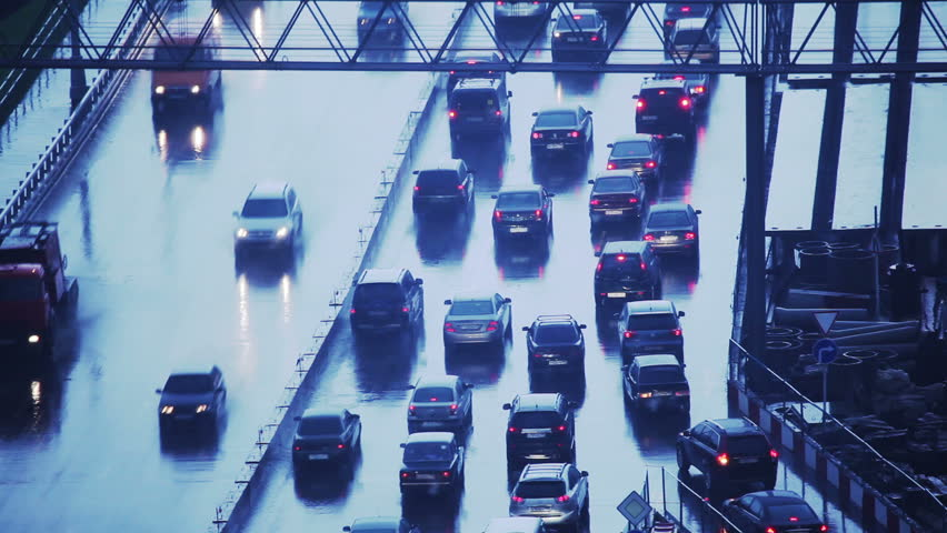 Many cars moving on freeway in traffic jam on a rainy day at twilight.