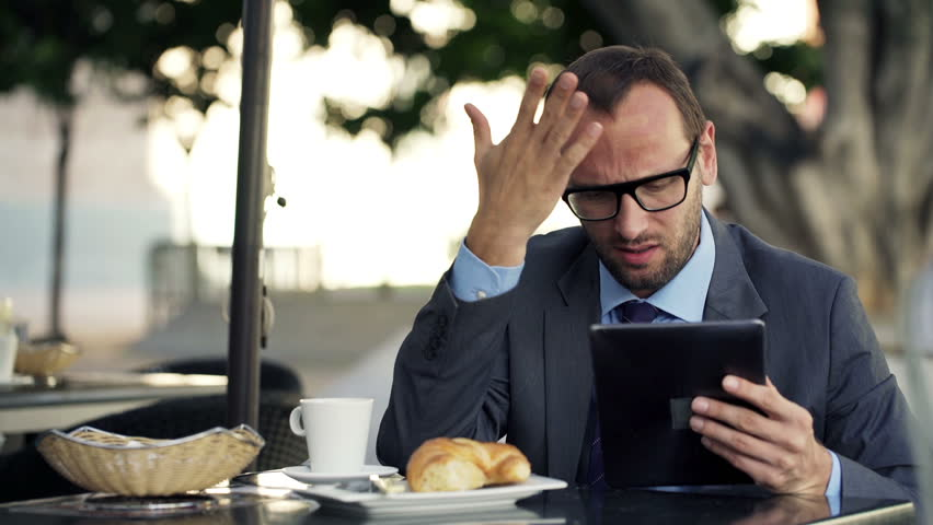 Unhappy businessman with smartphone and tablet computer reading bad news in cafe