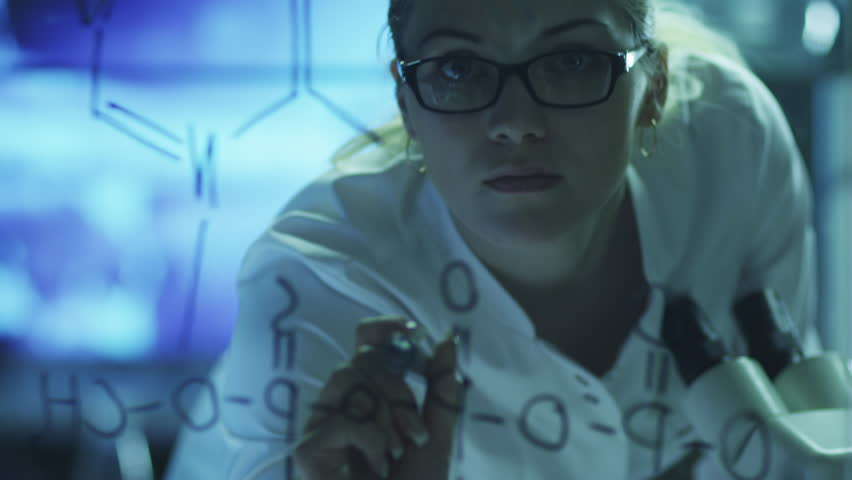 Woman Scientist is Drawing Organic Chemical Formulas on Glass. Shot on RED Cinema Camera in 4K (UHD). #9344678