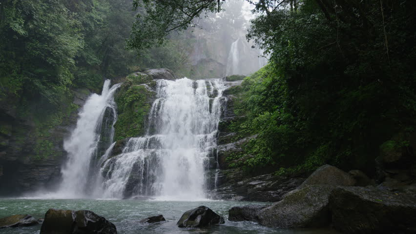 Wide panning slow motion view of waterfall in forest: Santa Juana, , Costa Rica