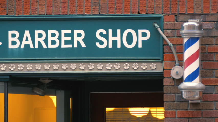 Barber shop sign and pole in city barbershop