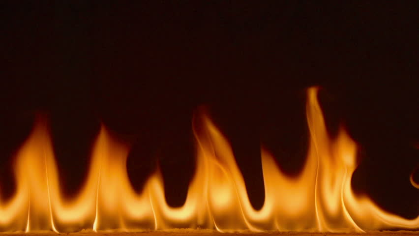 Super Slow Motion Of Clean Flames Igniting And Burning. A line of real flames ignite on a black background. Shot at 240fps this will look great in any fire or grill project. Real fire footage.