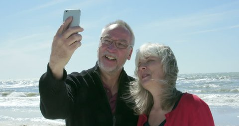 A happy, smiling senior couple take a selfie photo of themselves on the beach. Shot in 4K UHD slow motion.