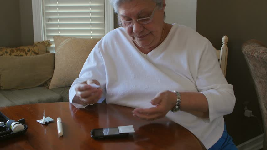 Diabetic mature woman checks her blood glucose level at home with her home glucose monitoring kit.