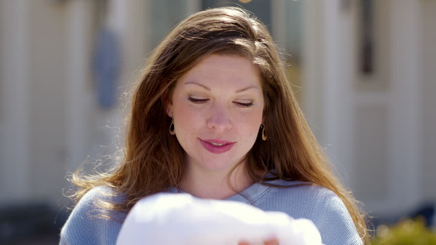 Medium close up of an attractive brunette in a powder blue sweater, smelling her clean sheets and smiling to the camera while outdoors on a sunny spring day.  Slow motion, recorded at 60fps in 4K.