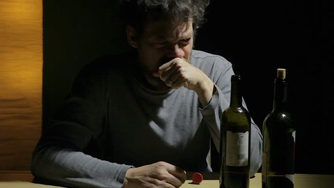 Desperate sad lonely alcoholic at home crying with empty bottles