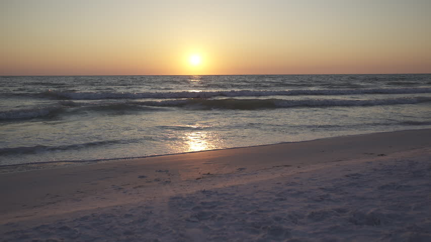 A woman and a man walk sit and relax on the shore of a beautiful vacation resort. The waves gentle wash along the beach as the couple enjoys the sunset or sunrise. The sand and the sea air