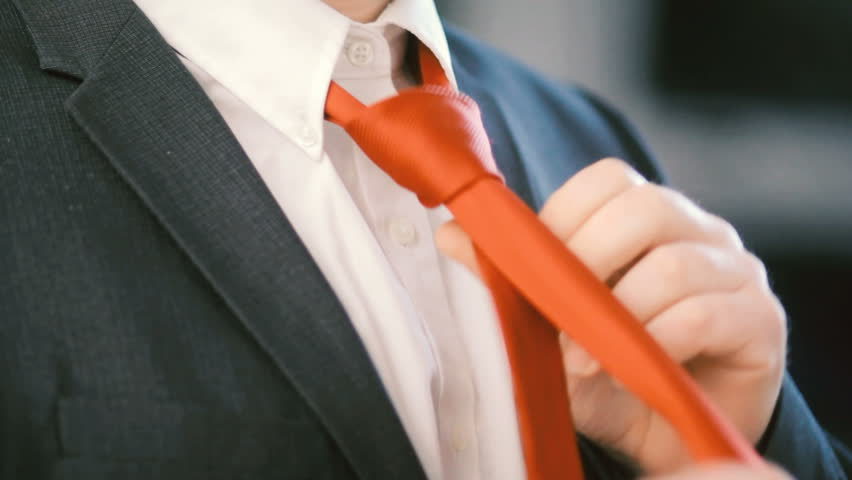 Man tying a neck tie putting on suit