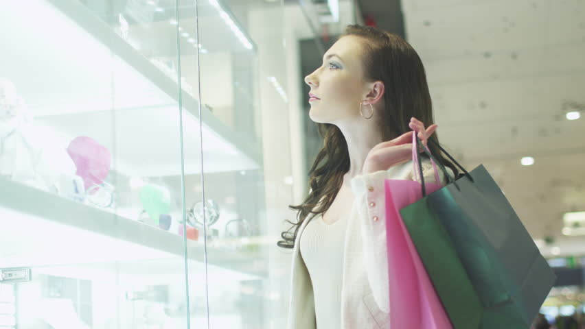 Young Pretty Girl with Shopping Bags is Looking at Display Window of Jewelry Store in Shopping Mall. Handheld Shot. Shot on RED Cinema Camera in 4K (UHD)