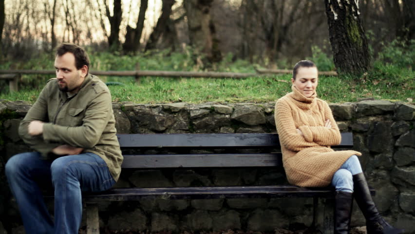 Relationship difficulties, young couple sitting on bench in the park
