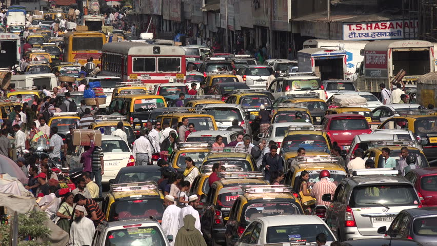 MUMBAI, INDIA - 8 NOVEMBER 2014: Traffic makes its way through a busy and chaotic street in front of a popular bazaar, during rush hour in Mumbai.