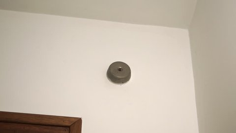 Metal wired door chime ringing on white wall.