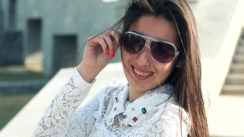fc093eacb4 Young beautiful girl in sunglasses. Pretty model poses outdoors in city  park footage full HD