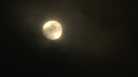 Full moon on dark, stormy night with clouds revealing and overtaking moonlight.