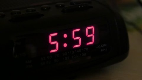 A man hits snooze when his alarm goes off at six in the morning