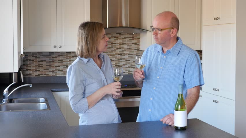Mature Middle Aged Baby Boomer Married Couple In Their Fifties Share A  Glass Of Wine In A Home Kitchen, Causally Dressed In A Designer Kitchen.