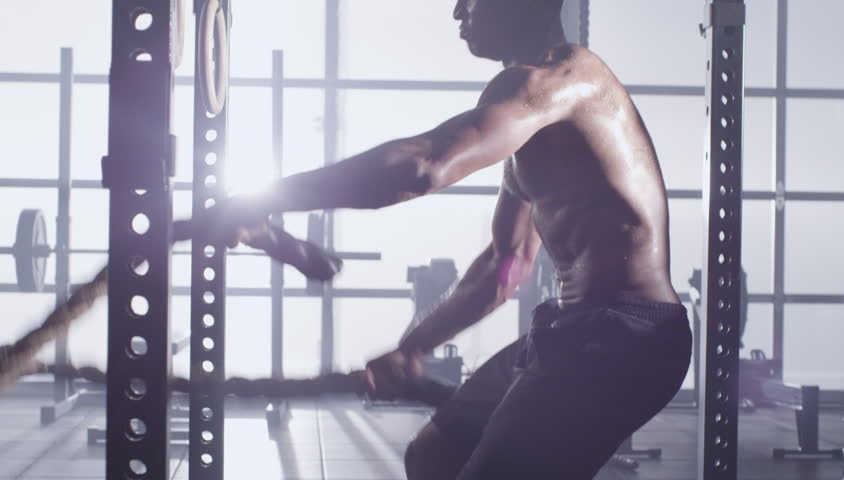 Medium shot slow mo tilt-up tilt-down young man exercising arms and shoulders with rope in gym side angle