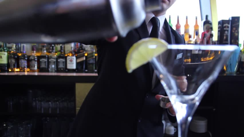 Barman makes a cocktail and than he pours it the cocktail glass