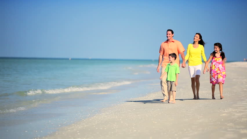 Attractive young family enjoying time together walking outdoors on the beach