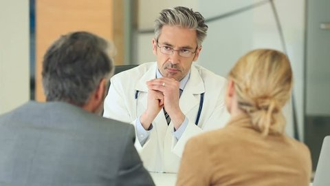 Doctor meeting couple in doctor's office