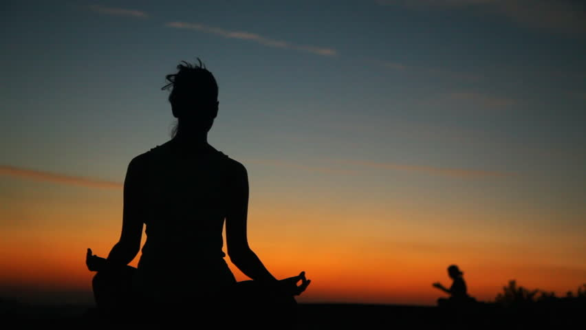 Silhouette of a girl meditating in the sunset. camera movement pan let to right | Shutterstock HD Video #9695468