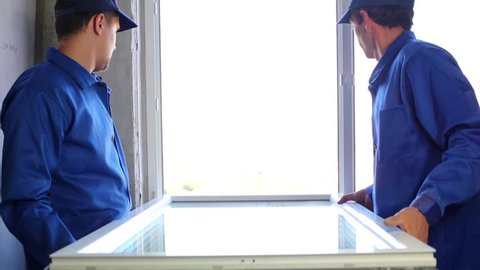 Two workers put window sash into new installed frame.