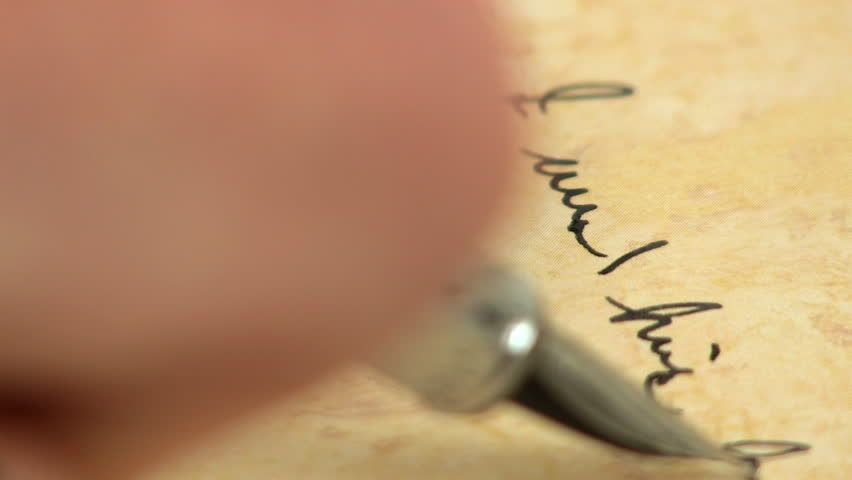 Macro of fountain pen tip gliding across the paper as it writes.